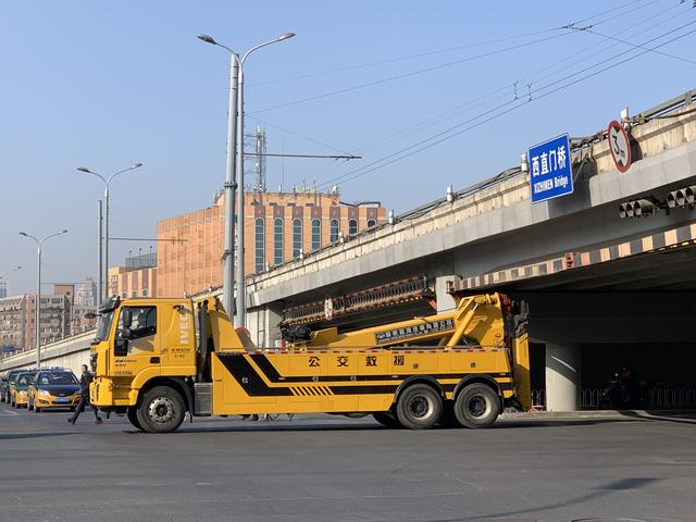 北京一大型公交救援车与西直门桥限高栏杆发生剐蹭,致限高栏晃动