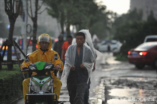 大雨突至路人打伞穿雨衣 看农民工环卫工这样应对